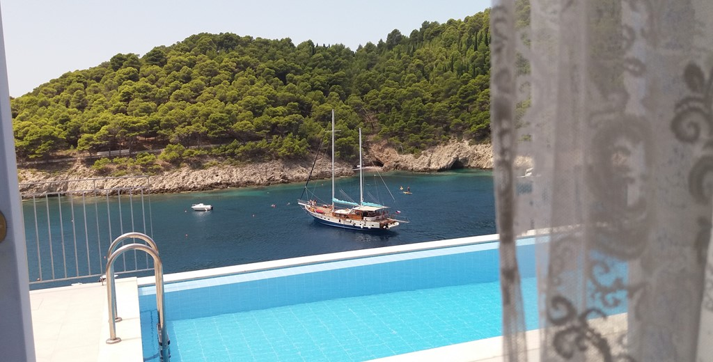 View from inside Villa Panorama looking out into the bay with yacht and private pool