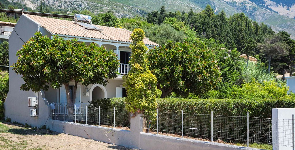 Lush green gardens and planting with the mountains as a backdrop at Beachfront Suites, Lourdata, Kefalonia