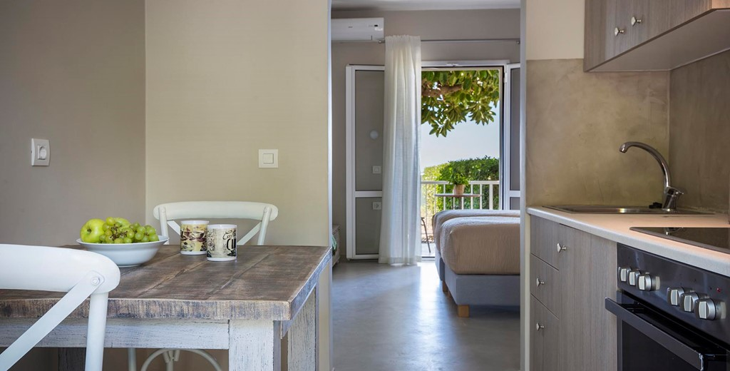 Kitchen, dining and views toward the sea through the French doors inside Beachfront Suite No2, Lourdata, Kefalonia