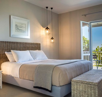 Double bed and French doors onto the balcony with views of the sea at Beachfront Suite No3, Lourdata, Kefalonia