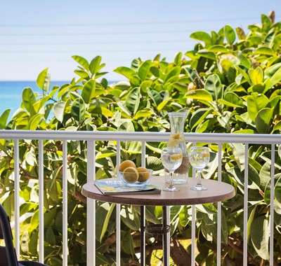 Drinks in the treetops on the balcony with sea views from Beachfront Suite No3, Lourdata, Kefalonia