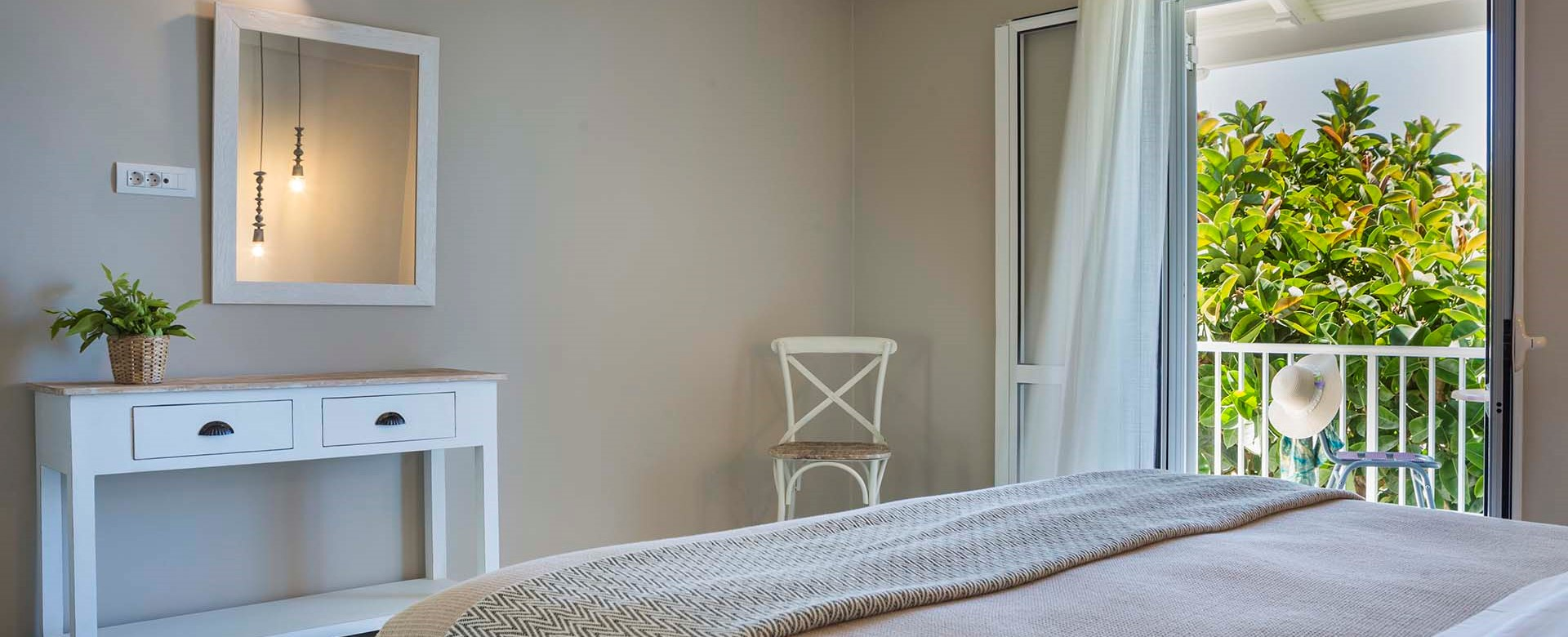 Double bed and French doors onto the balcony with views of the sea at Beachfront Suite No4, Lourdata, Kefalonia