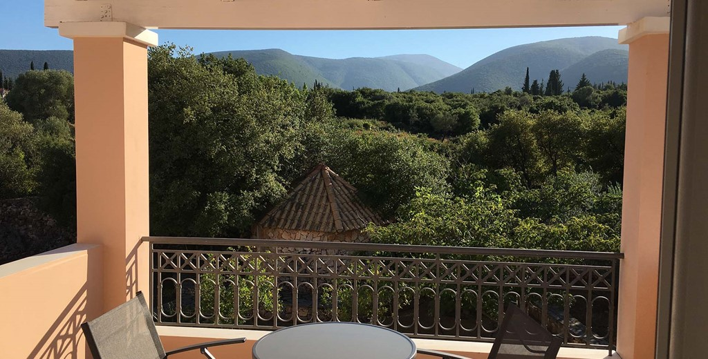 Share a holiday drink with mountain views on the veranda at Casa Angela, Melissani Apartments, Karavomilos, Kefalonia, Greek Islands