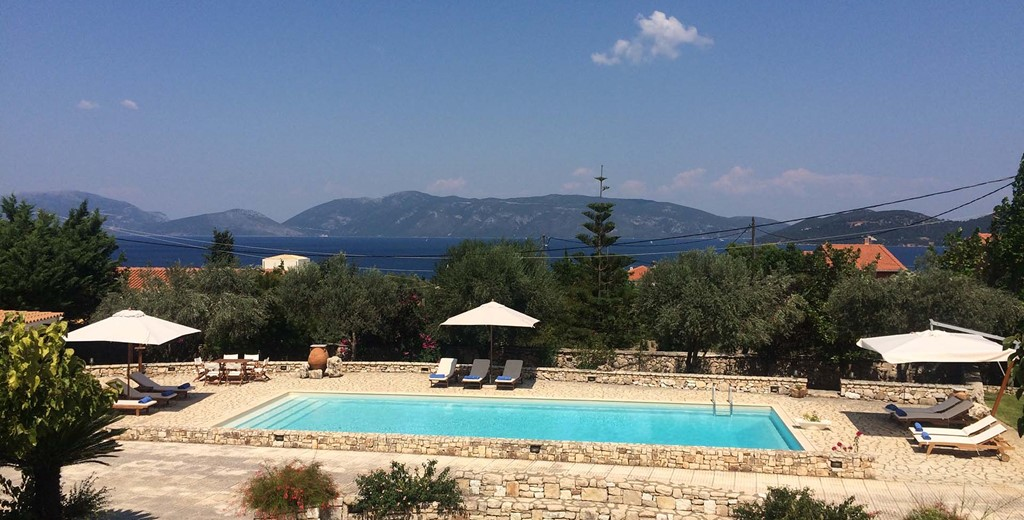 Pool Sun loungers sea and mountain views at Casa Angela, Melissani Apartments, Karavomilos, Kefalonia, Greek Islands