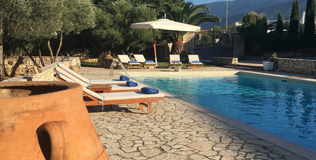 Sun beds beside the pool prepared for another great holiday in Casa Elena, Melissani Apartments, Karavomilos, Kefalonia, Greek Islands