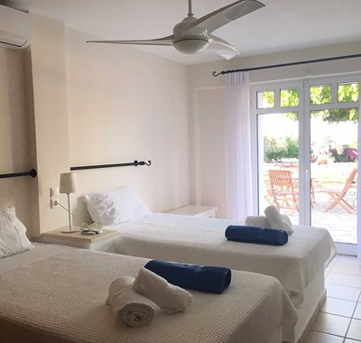 Bedroom with single beds and French doors opening onto the patio at Casa Elena, Melissani Apartments, Karavomilos, Kefalonia, Greek Islands