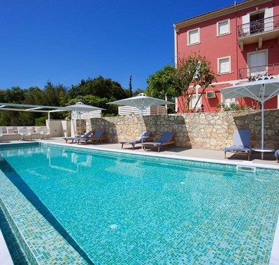 Pool and sun beds ready for a long holiday sunbathing outside Magnolia Apartments, Fiscardo, Kefalonia, Greek Islands