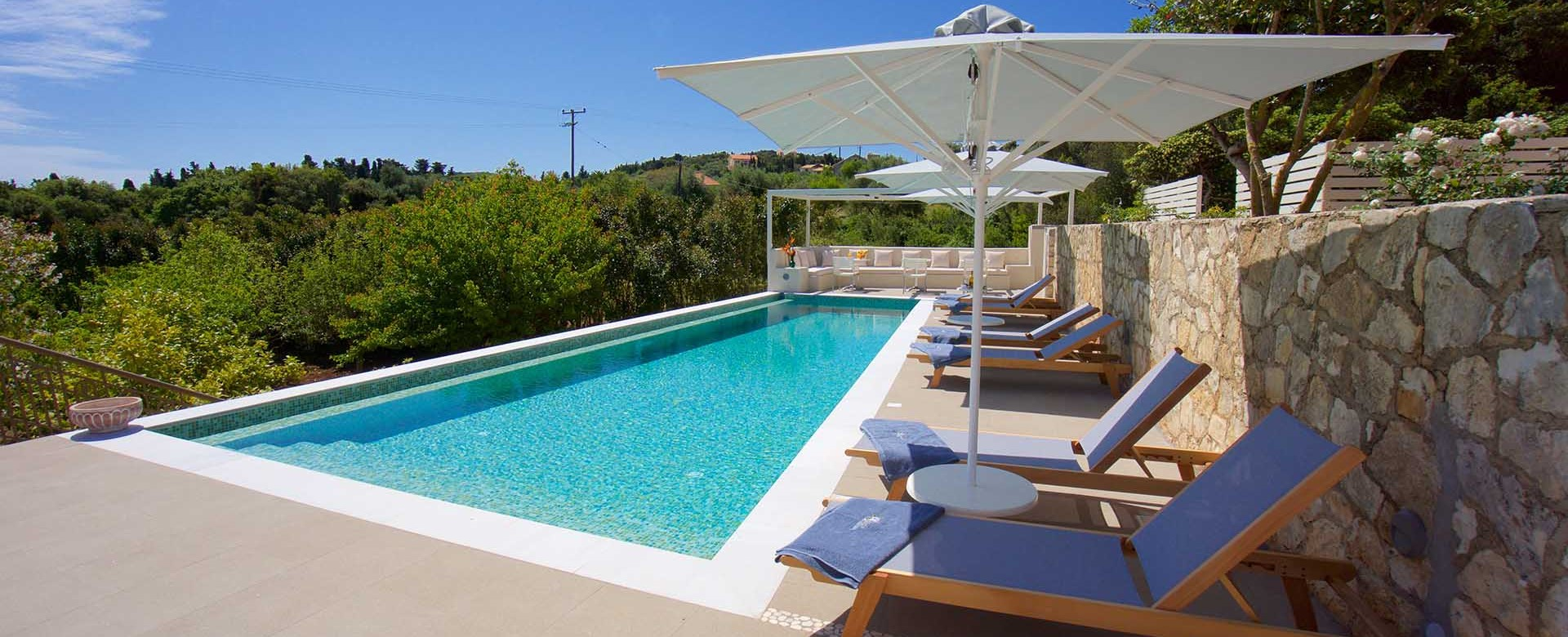 Pool sun beds and green views from Magnolia Apartments, Fiscardo, Kefalonia, Greek Islands