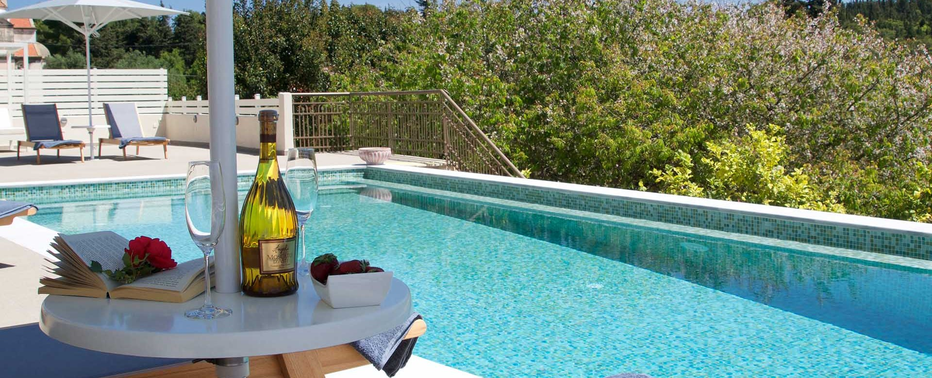 Get maximum holiday relaxation with a good book and good wine by the pool at Magnolia Apartments, Fiscardo, Kefalonia, Greek Islands