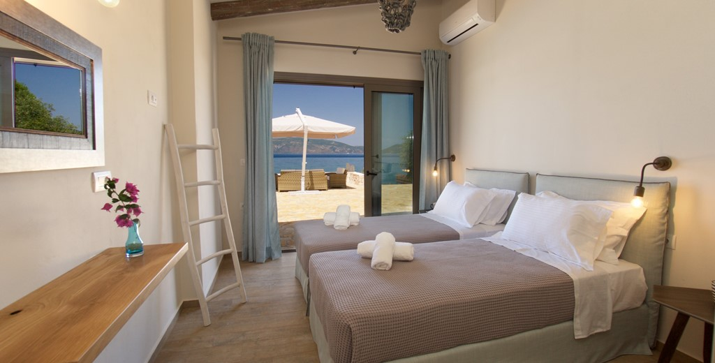Bedroom with a view, twin beds and wide opening doors inside Villa Frydi, Karavomilos, Kefalonia, Greek Islands