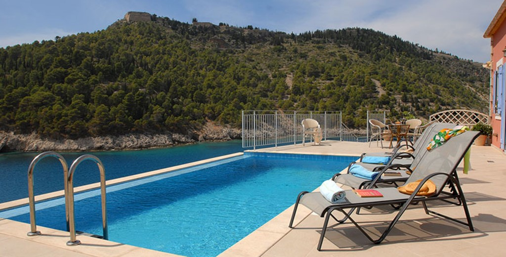 Infinity pool, sun loungers and view of the hill outside Villa Panorama, Assos, Kefalonia