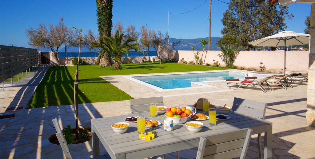 Outside dining with a view across manicured gardens and pool at Villa Theano, Sami, Kefalonia, Greek Islands