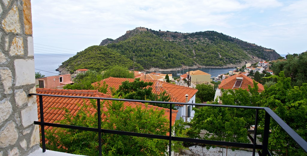 View over the rooftops toward the sea and ruined Venetian fort outside Villa Vivere, Assos, Kefalonia