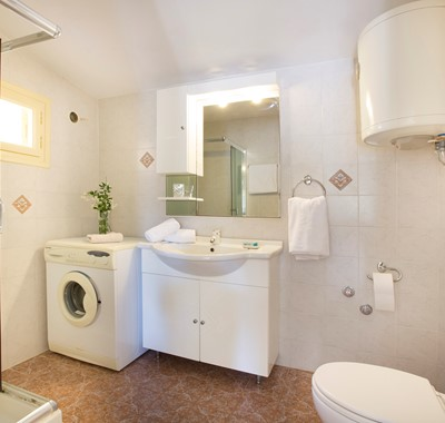 Bathroom with shower and washing machine inside Lemoni Cottage, Fiscardo, Kefalonia