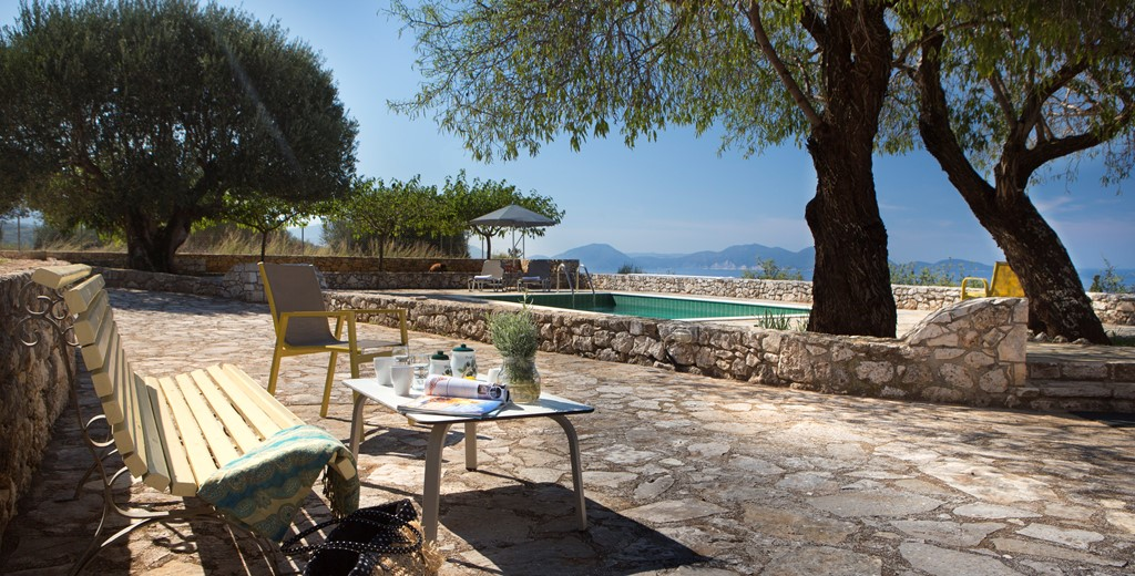 Bench to relax on during the afternoon sun with trees for shade outside Lemoni Cottage, Fiscardo, Kefalonia