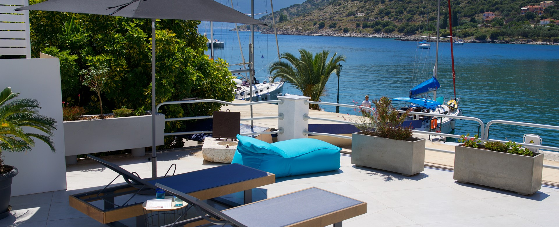 Sunbeds and lounging outside in the sun on the waterfront at Palm House Harbourfront Mansion, Agia Efimia, Kefalonia, Greek Islands