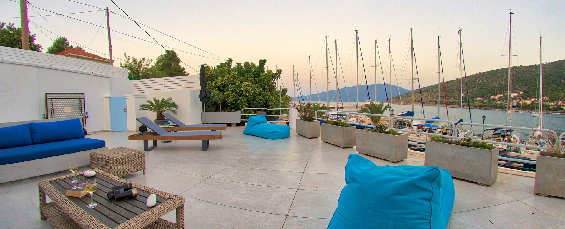 Spacious open patio terrace right on the waterfront with moored yachts outside Palm House Harbourfront Mansion, Agia Efimia, Kefalonia, Greek Islands