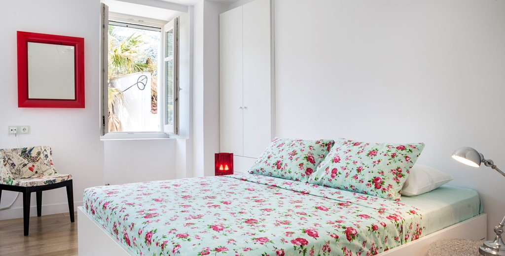 Spacious bedroom with double bed and open window inside Palm House Harbourfront Mansion, Agia Efimia, Kefalonia, Greek Islands