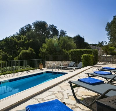 Sun beds and pool sorrounded by lush green trees in Villa Cypress, Fiscardo, Kefalonia, Greek Islands