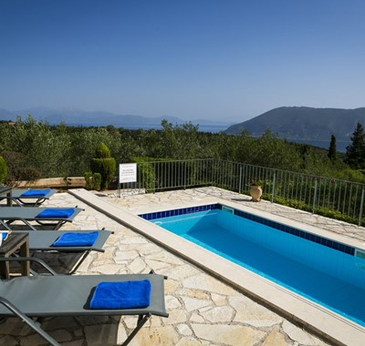 Sun loungers and pool with views from the terrave of the coastline and mountains of Kefalonia, Greek Islands