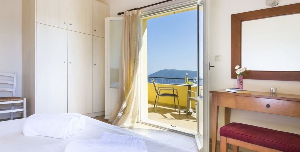 Bedroom with its own balcony and plenty of storage for you possessions during your holiday to Villa Cypress, Fiscardo, Kefalonia, Greek Islands