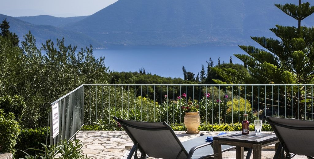 Sun beds on the terrace surrounded by lush gardens around Villa Cypress, Fiscardo, Kefalonia, Greek Islands