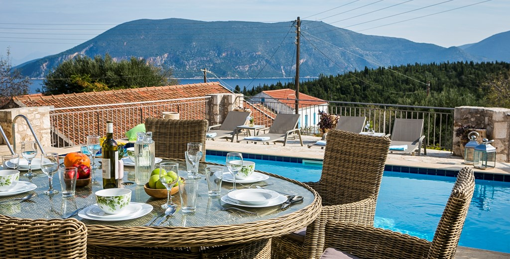 Al fresco dining beside the pool with a view of the cost and mountains outside Villa Pelagia, Fiscardo, Kefalonia, Greek Islands